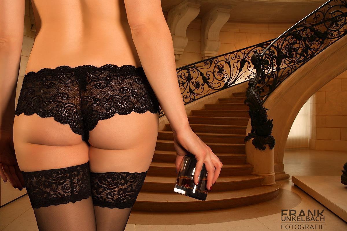 Frau mit erotischer Reizwäsche und einem Glas Whiskey im Treppenhaus (Dessous)