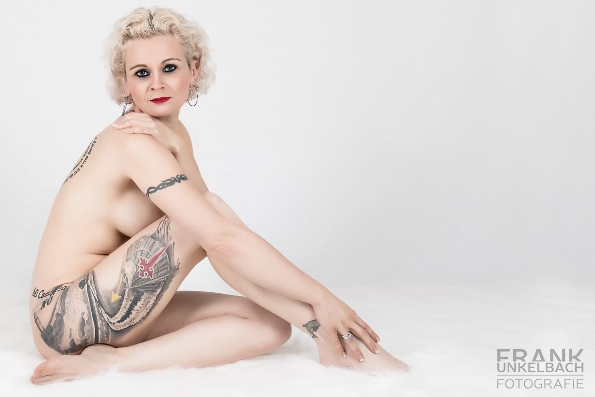 Verdeckter Akt einer blonden Frau auf einem weißen Fell (Akt)