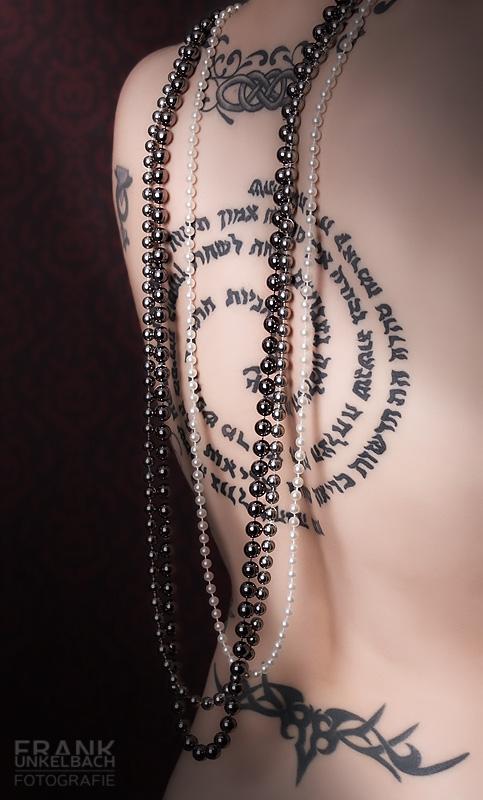 Tätowierter Rücken einer Frau mit Perlenketten. (People)