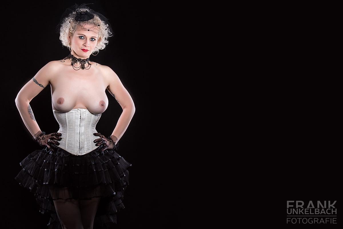 Blonde Frau mit nackten Brüsten in Korsett und elegantem Rock (Fashion)