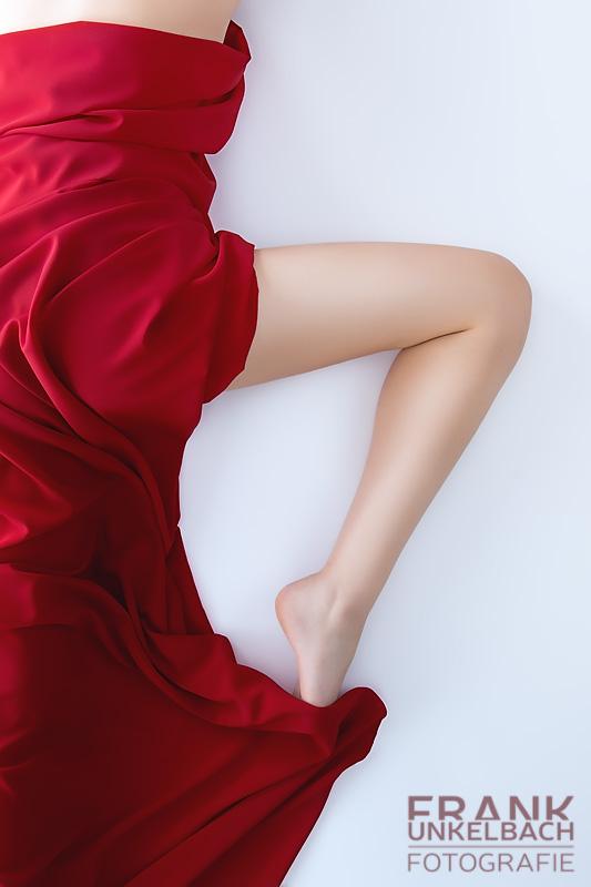 Sexy schlankes Frauenbein schaut unter einem roten Tuch hervor (People)