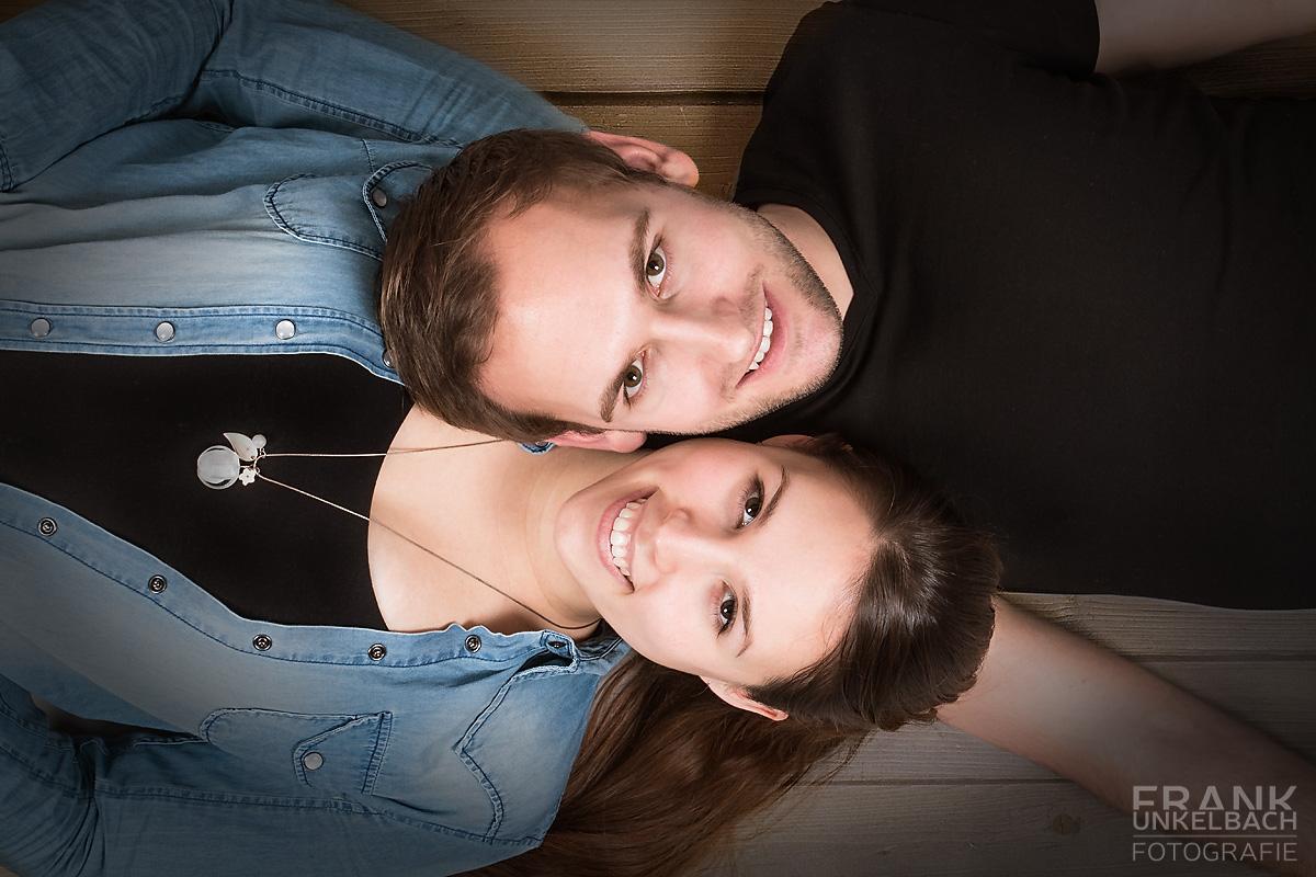 Strahlendes Paar Wange an Wange auf dem Boden liegend (People)