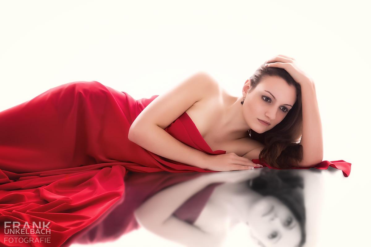 Frau eingehüllt in eine rotes Tuch auf einem Spiegel (People)