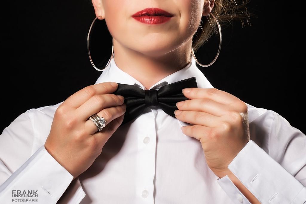 Frau mit weißem Hemd richtet Ihre schwarze Fliege (Fashion)
