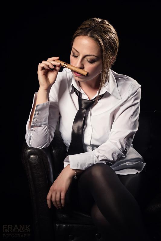 Frau in Hemd und Krawatte mit Zigarre im Sessel (People)