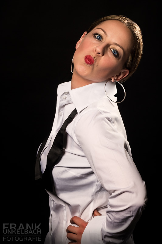 Frau in weißem Hemd und ungebundener Fliege macht einen Kussmund (Portrait)