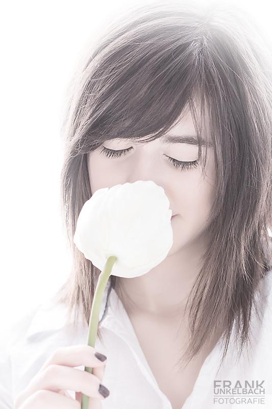 Junge Frau riecht mit geschlossenen Augen an einer weißen Rose (High Key - Portrait)