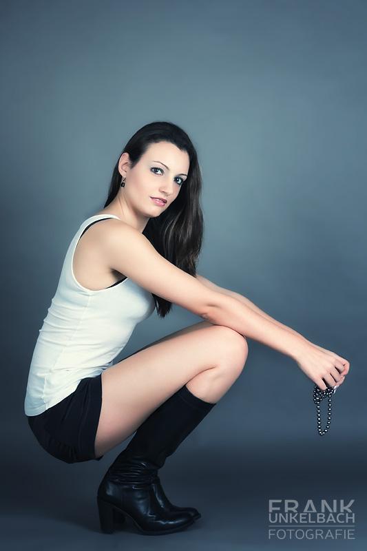 Frau mit schwarzer Hot Pant und Stiefeln in der Hocke (Fashion)