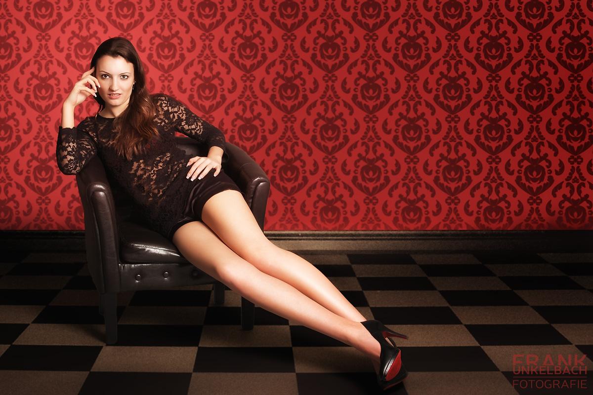 Frau mit langen Beinen und High Heels im Sessel