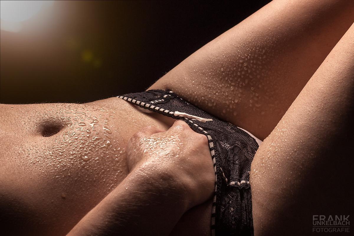 Mit Wassertropfen bedeckte Frau greift sich mit der Hand in den Slip (Dessous)