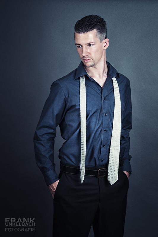 Portrait eines smarten Manns mit dunklem Anzug und ungebundener heller Krawatte (People)