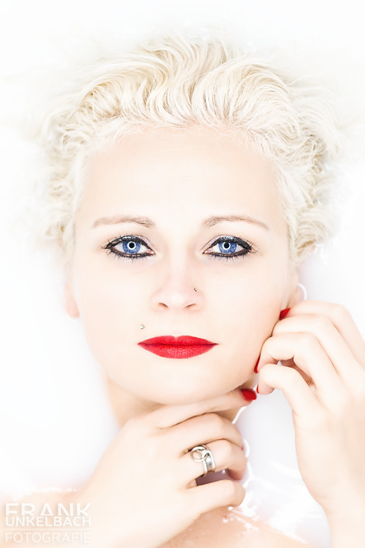 Portrait einer blonden Frau mit blauen Augen und roten Lippen im Milchbad (Portrait)