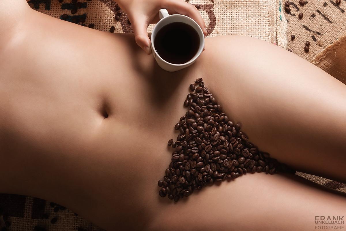 Intimbereich einer Frau mit Kaffeebohnen bedeckt und einer Tasse Kaffee in der Hand.