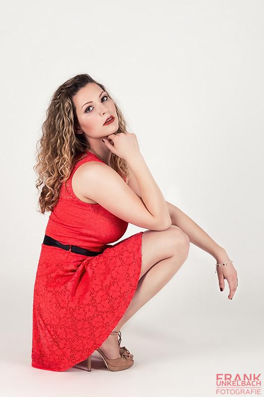 Frau sitzt mit einem roten Kleid in der Hocke (Fashion)