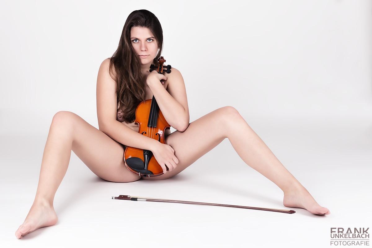 Schüchterne Frau mit provokant gespreizten Beinen und Geige im Arm (Akt)