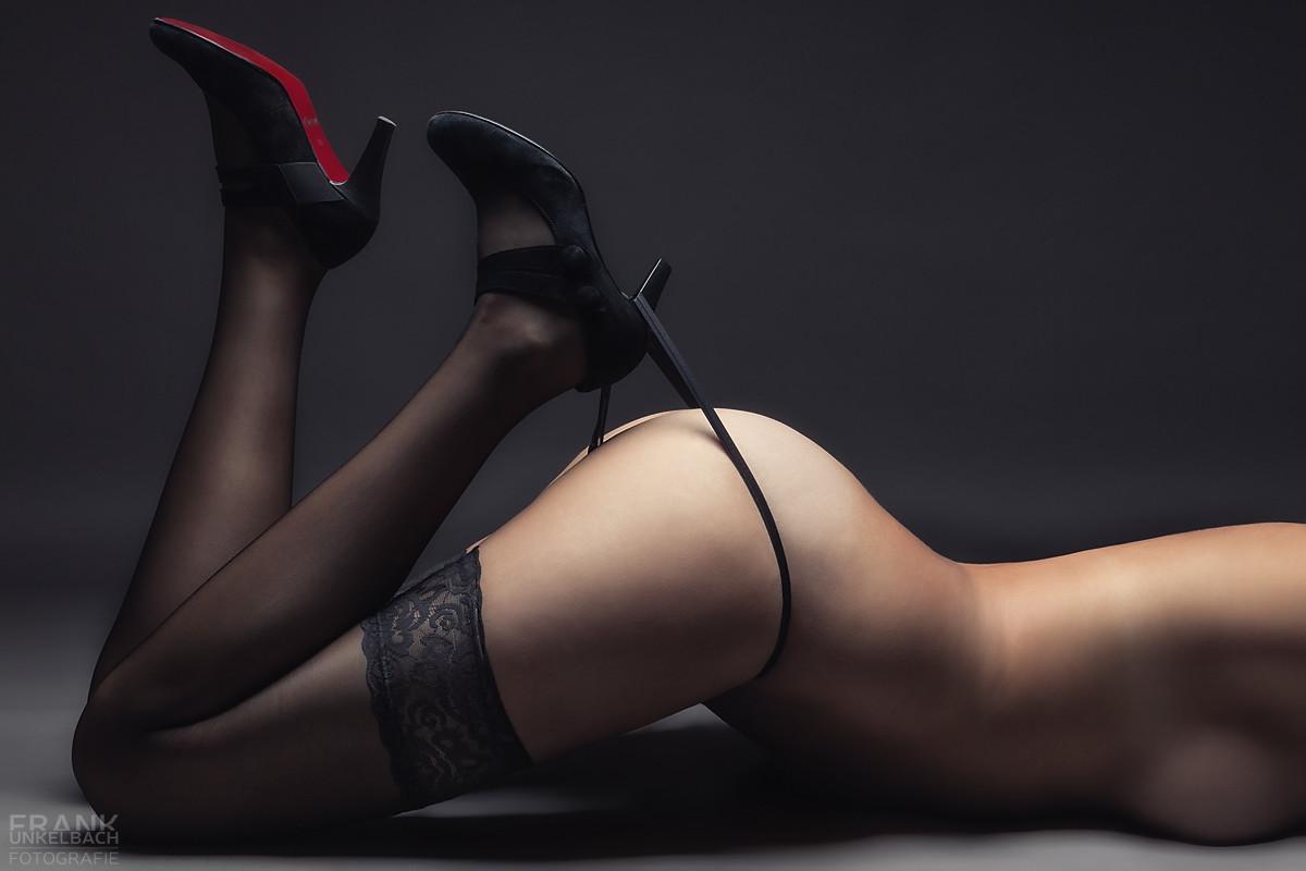 Frau mit halterlosen Strümpfen und in die Higt Heels eingehaktem String (Akt)