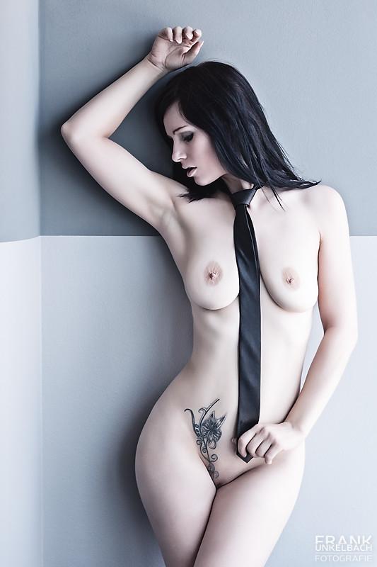 Nackte Frau steht nur mit einer schwarzen Krawatte bekleidet an der Wand (Akt)