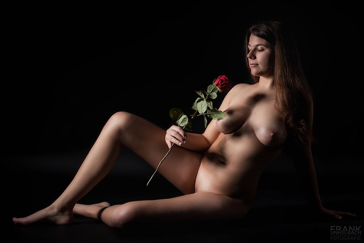 Frau sitzt nackt mit einer langstieligen Rose auf dem Boden (Akt)
