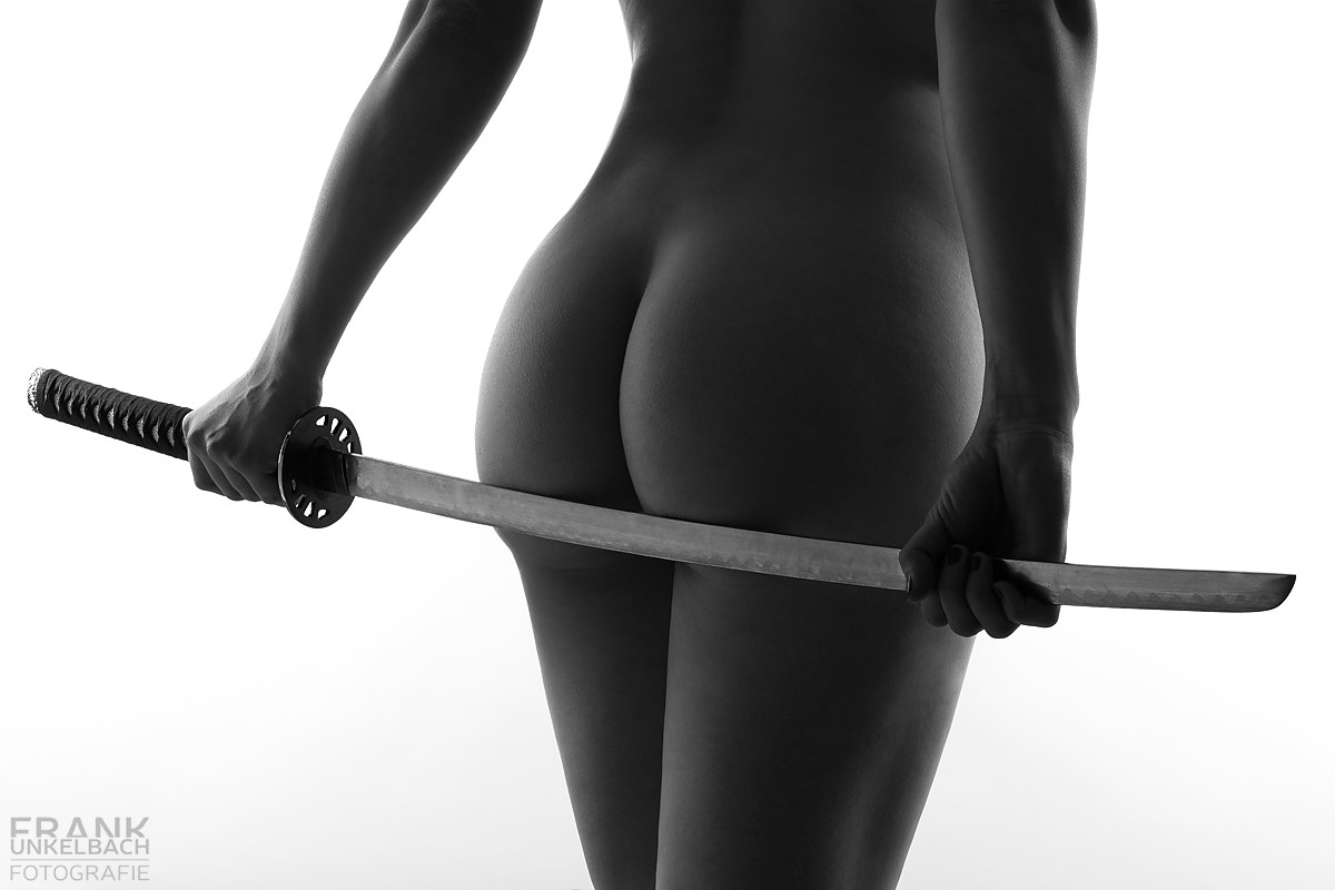 Frau hält sich ein japanisches Schwert (Katana) an den Po. (Akt)