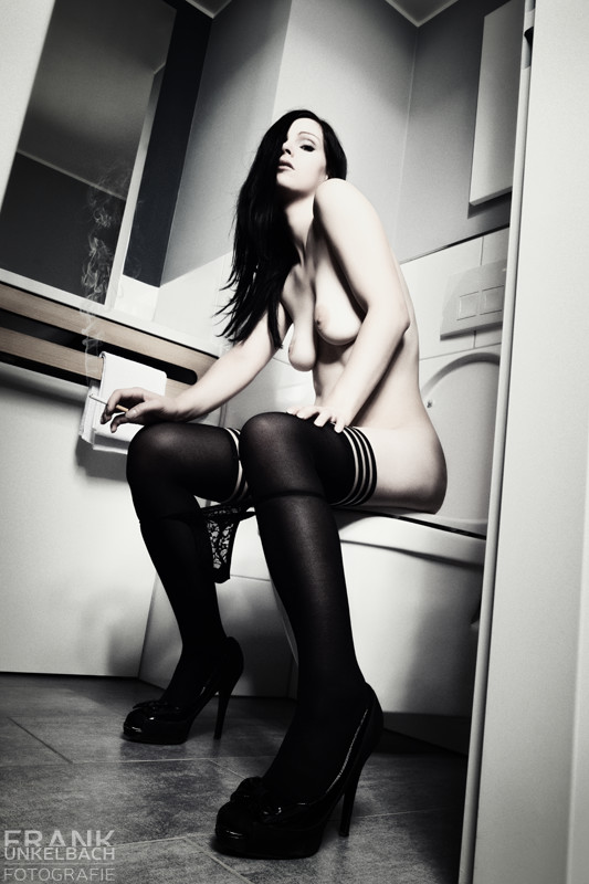 Frau sitzt mit Slip zwischen den Knien und Zigarette auf der Toilette. (Akt)