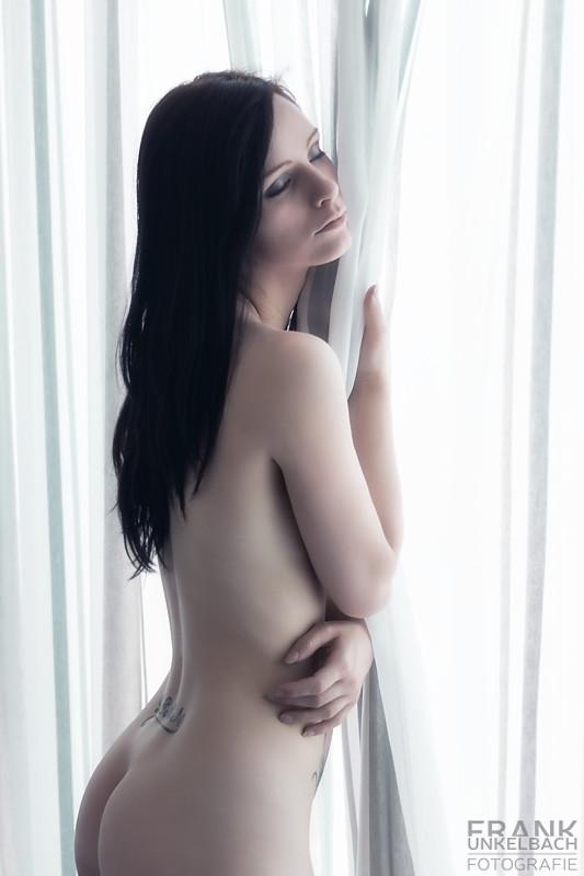 Nackte Frau steht am Fenster mit dem Vorhand im Arm. (Akt)
