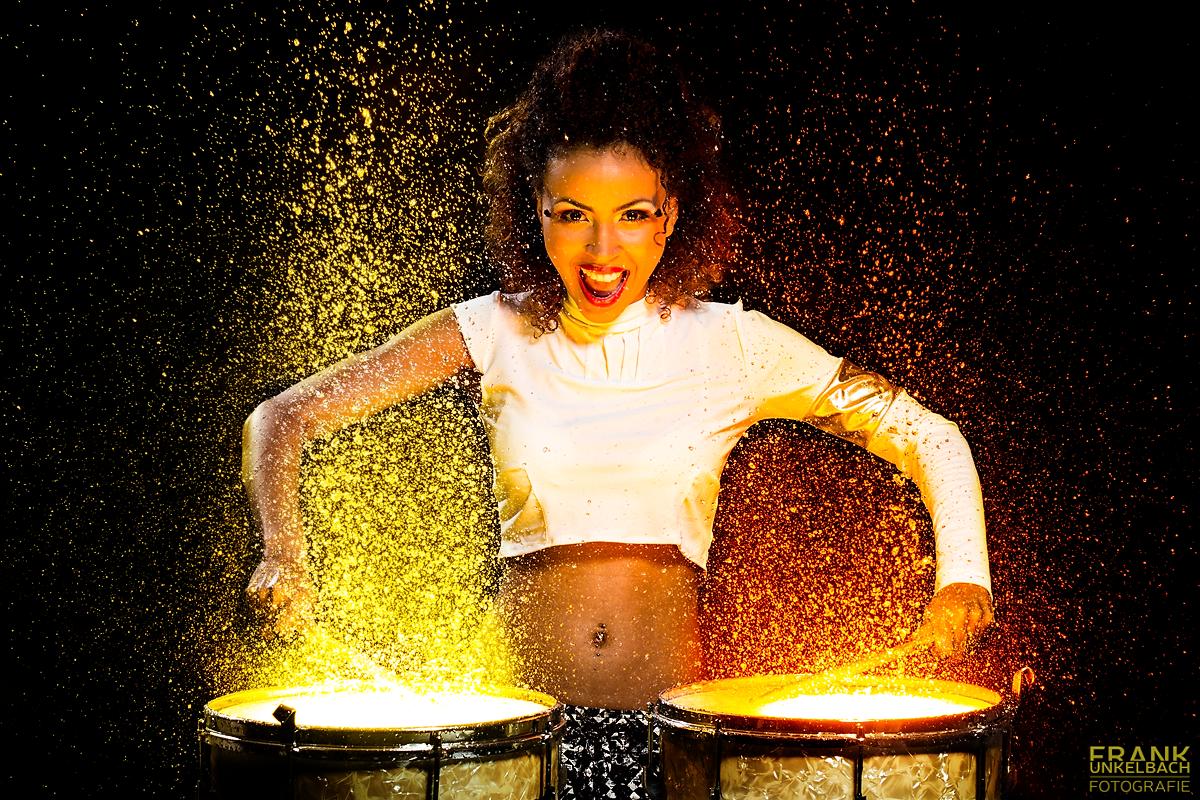 Farbenfrohes Portrait einer Frau, die auf mit Wasser bedeckten Trommel spielt (People)