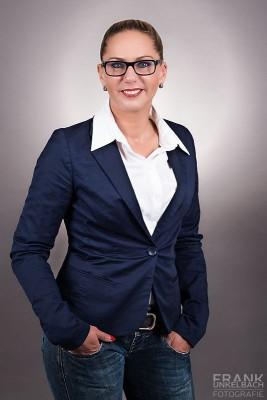 Business-Portrait einer Frau mit Brille, weißer Bluse und blauem Jacket. (Business)