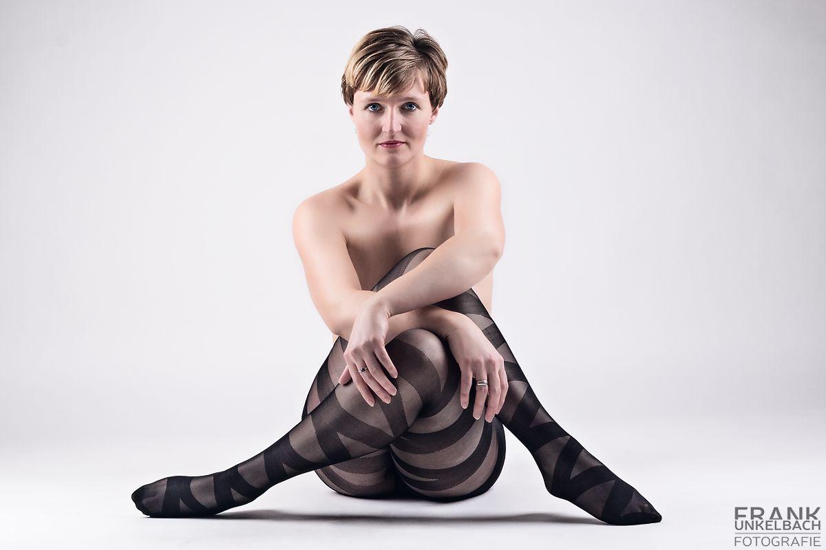 Frau in gestreifter Strumpfhose sitzt mit verschränkten Armen und Beinen auf dem Boden (Fashion)