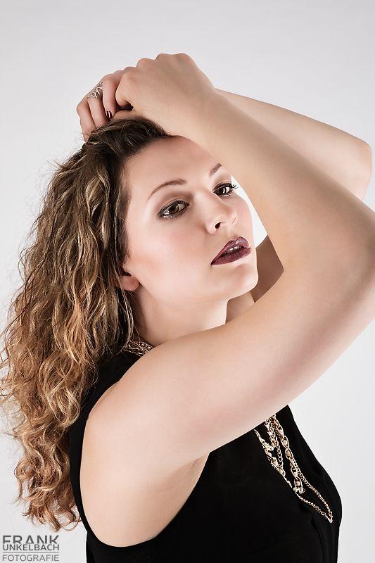 High-Fashion Portrait einer Frau mit schwarzem Oberteil und Goldschmuck (Portrait)