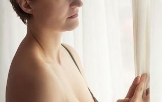 Junge Frau steht mit BH bekleidet am Fenster und blickt in die Ferne (Portrait)