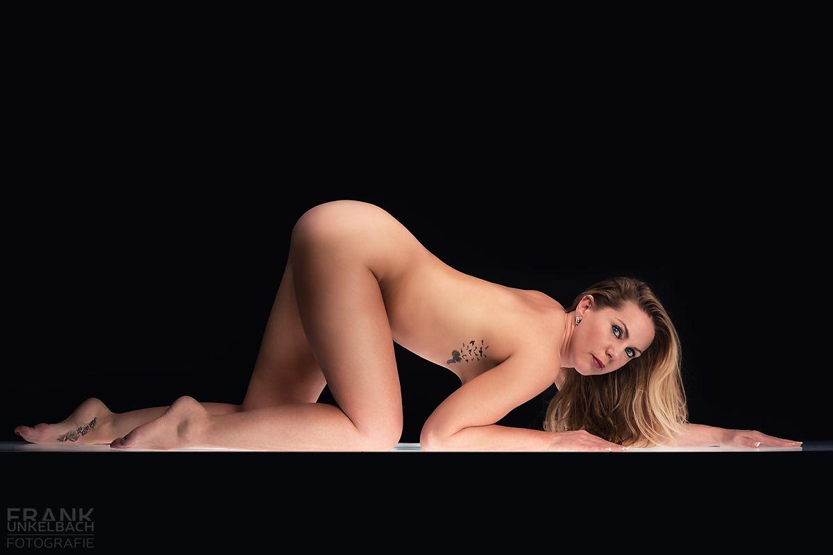 Tätowierte nackte Frau in katzenartiger Pose auf einem Lichttisch (Akt)