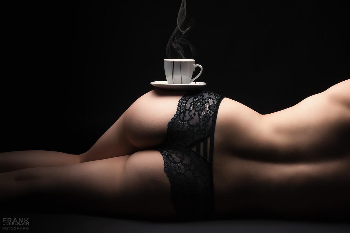 Dampfende Kaffeetasse auf der Hüfte einer sexy Frau mit Spitzenslip. (Dessous)