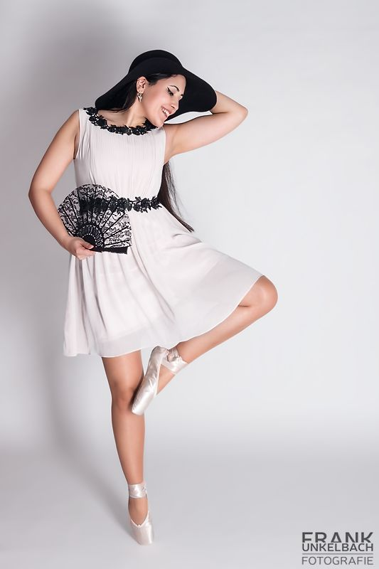 Ballerina tanzt mit weißem Kleid sowie schwarzem Hut und Fächer (Fashion)