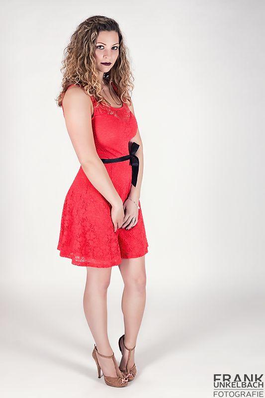 Junge Frau in schüchterner Pose mit rotem Kleid und High Heels (Fashion)