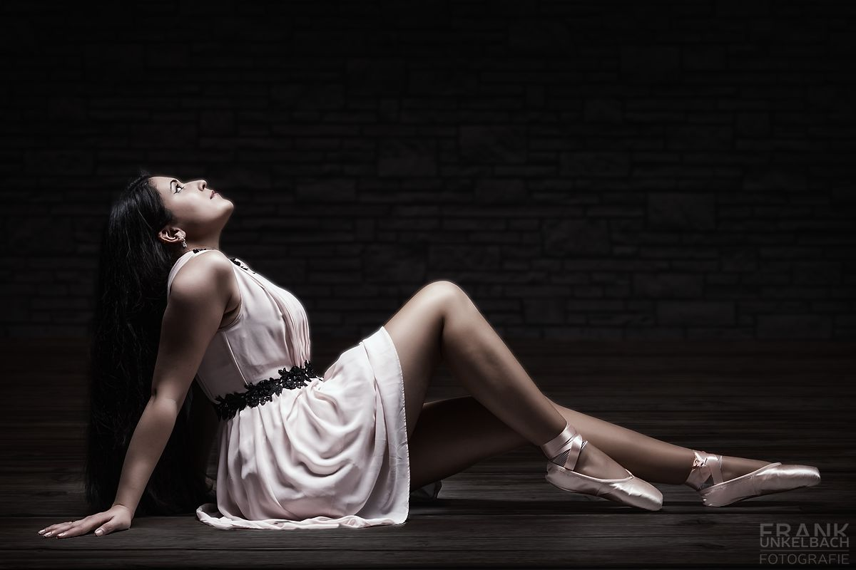 Ballerina sitzt in einem rosa Kleid in einem dunklen Raum (People)