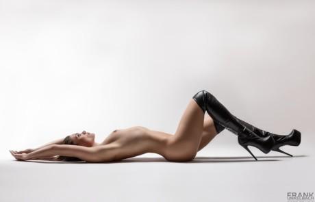 Frau liegt nur mit Overknees bekleidet auf dem Rücken (Akt)