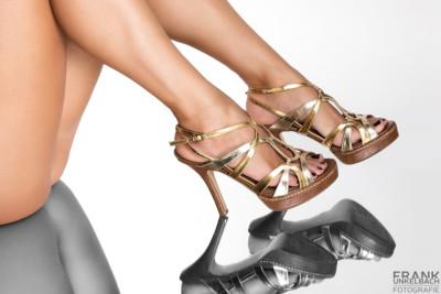 Lange Beine mit goldenen High Heels auf einem Spiegel (Akt)
