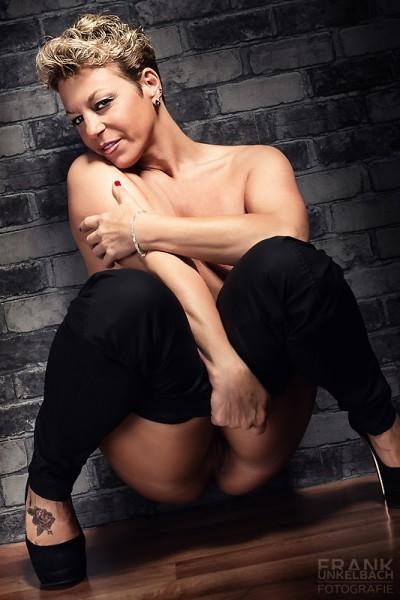 Nackte Frau mit High Heels sitzt mit heruntergelassenere Hose an der Wand. (Akt)