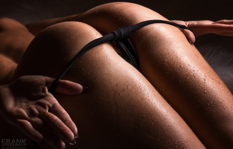 Frau streift sich einen Tanga über Ihren mit Wassertropfen bedeckten Po (Akt)