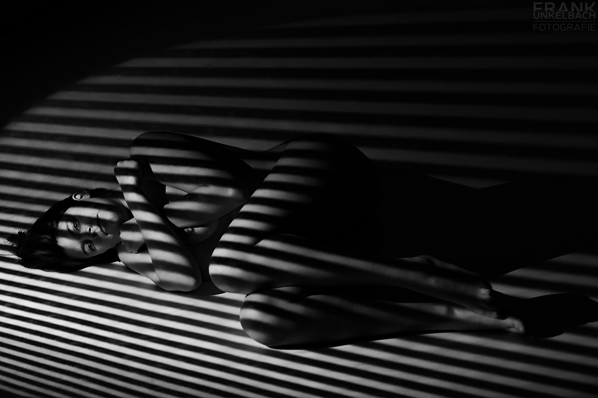 Frau liegt nackt auf dem Boden und wird mit Lichtstreifen beschienen.