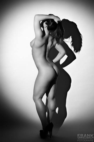 Der Schatten einer nackten Frau mit Pferdeschwanz fällt auf eine weiße Wand.
