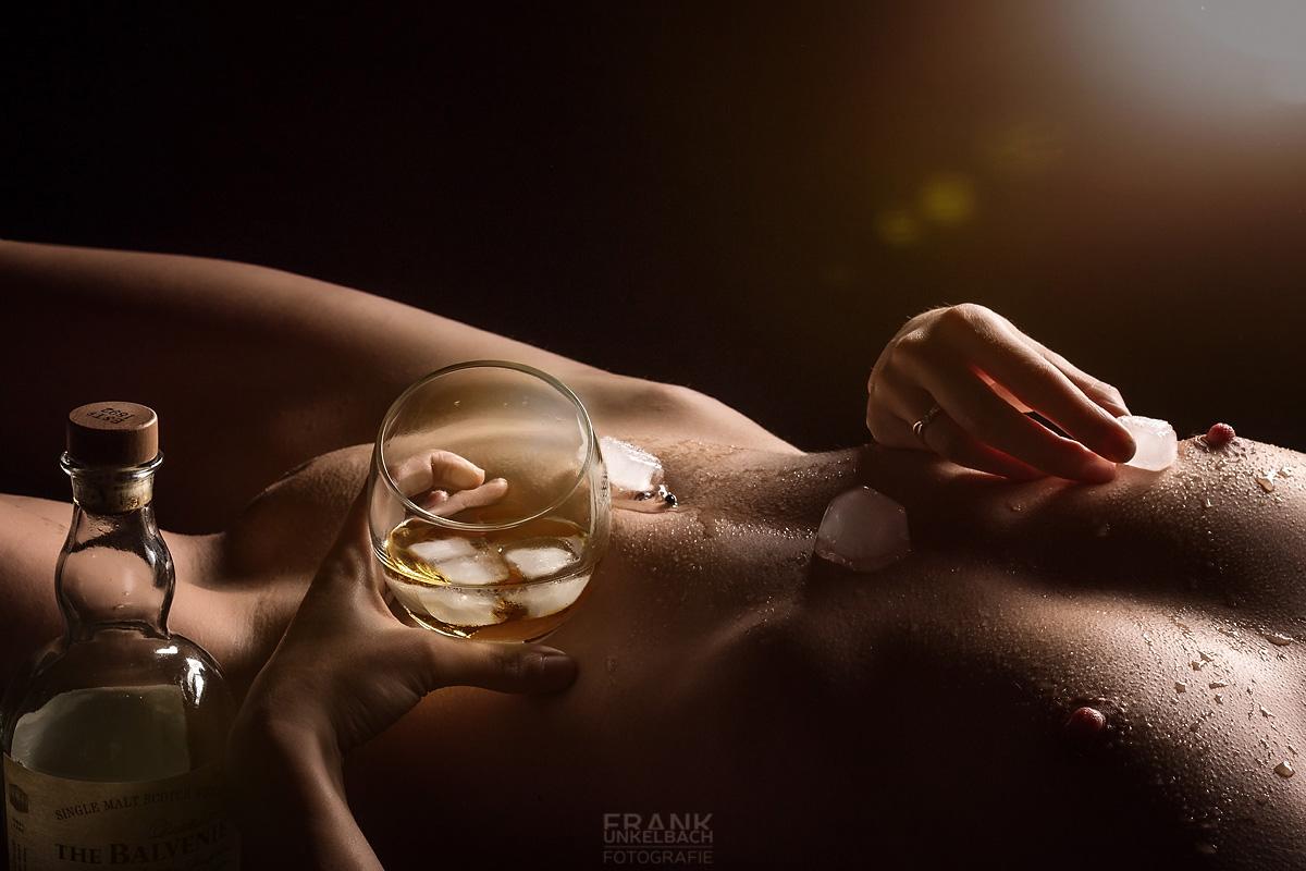 Nackte Frau mit Eiswürfeln auf der Haut und einem Glas Whiskey in der Hand