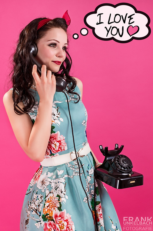 Junge dunkelhaarige Frau im 50er-Jahre Stil (Rockabilly) gekleidet telefoniert mit einem alten Telefon.