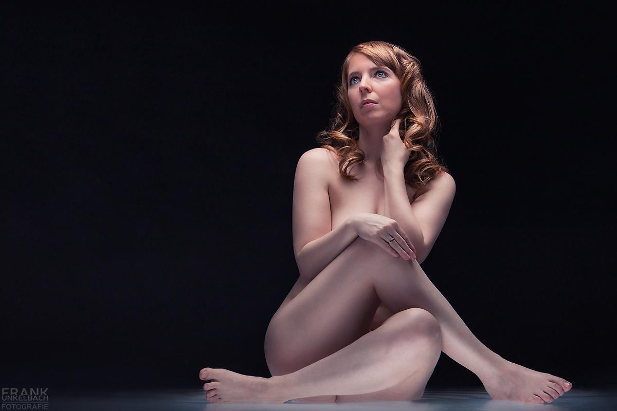 Junge nackte Frau mit roten Haaren und blauen Augen sitzt mit verschränkten Beinen auf einem Leuchttisch und schaut verträumt in die Ferne.