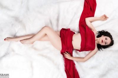 Junge nackte Frau im Schneewittchen-Look liegt nur von einem roten Tuch umhüllt auf einem weißen Fell.