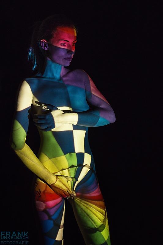 Der nackte Körper einer jungen Frau dient als Leinwand für ein farbenprächtiges Muster