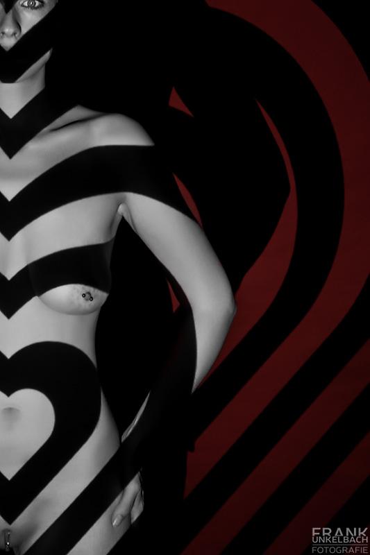 Mittels eines Beamers wird ein Muster aus Herzen auf eine junge nackte Frau projiziert.