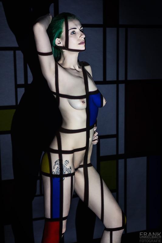 Junge sexy Frau mit grünen Haaren wird mittels eines Beamers in ein Kunstwerk von Mondrian integriert.