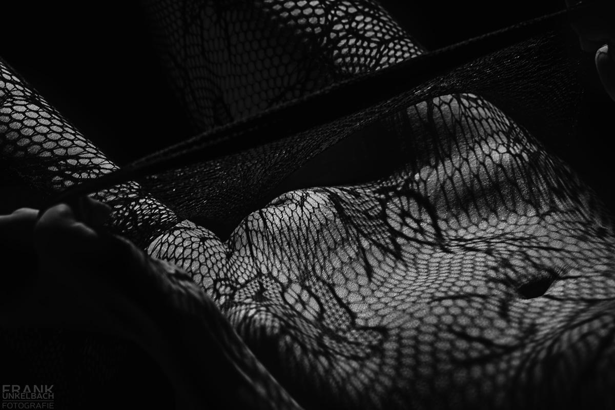 Der Schatten einer Netzstrumpfhose fällte auf Beine, Intimbereich und Bauch einer nackten Frau.
