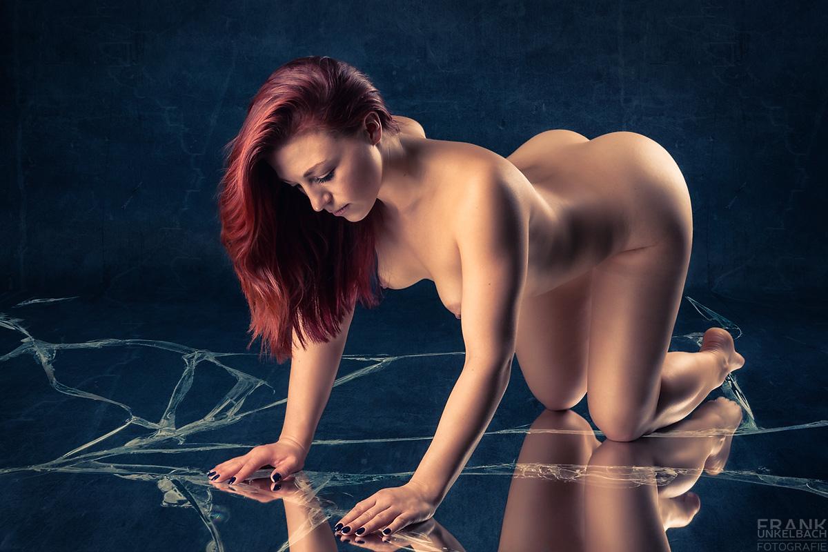 Rothaarige sexy Frau kniet nackt auf dem Boden und blickt in einen zerbrochenen Spiegel